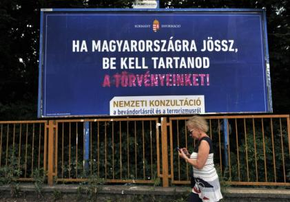 "FOR STORY: HUNGARY BILLBOARD BATTLE - A woman is walking in front of a vandalized anti immigration billboard reading ""If you come to Hungary, you have to respect our laws!"" in Budapest, Hungary, on June 15, 2015. Hungary's central-right government has launched a controversial billboard campaign against immigration while UNHCR introduced its counter campaign highlighting successful refugee stories. (AP Photo/Bela Szandelszky)"
