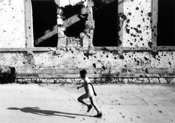 παιδι μπροστά από κατεσραμμένο σπίτι στο Μόσταρ