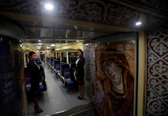 Train hostesses stand in a train carriage decorated with iconic religious figures as it departs from Belgrade to Mitrovica, Kosovo at Belgrade's railway station, Serbia, Saturday, Jan. 14, 2017. Serbia has launched a railway link to Serb-dominated northern Kosovo despite protests from authorities in Pristina who described the move as a provocation and an aggressive violation of Kosovo's sovereignty. (AP Photo/Darko Vojinovic)